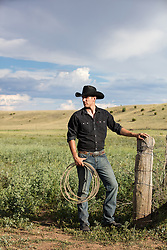 All American chiseled cowboy leaning on a fence at a ranch
