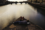 Young couple lounges on the bridge over the Arno River Florence, Italy.