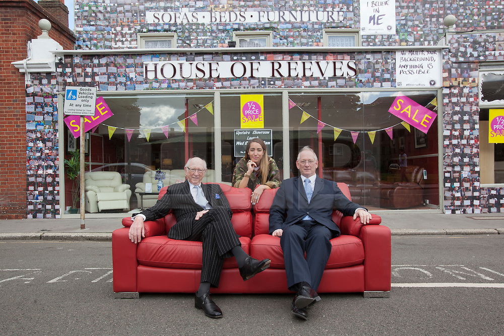 """© licensed to London News Pictures. London, UK 06/08/2012. Maurice (L) and Trevor Reeves (R), the owners of the House of Reeves furniture store and British singer-songwriter Delilah (centre) posing outside the shop which was burnt down in last year's riots. The shop has been covered in 4000 images of young people with positive messages on August 6, 2012 in Croydon. The youth volunteering charity """"vInspired"""" are marking the one year anniversary of the riots in Croydon by displaying thousands of images of young Britons holding up positive messages about themselves on the House of Reeves furniture store which was destroyed in last year's violence. British singer-songwriter Delilah is one of the supporters of the volunteering charity """"vInspired"""". Photo credit: Tolga Akmen/LNP"""