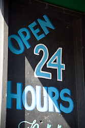 Sign in front of shop selling alcoholic drinks 24 hours a day,