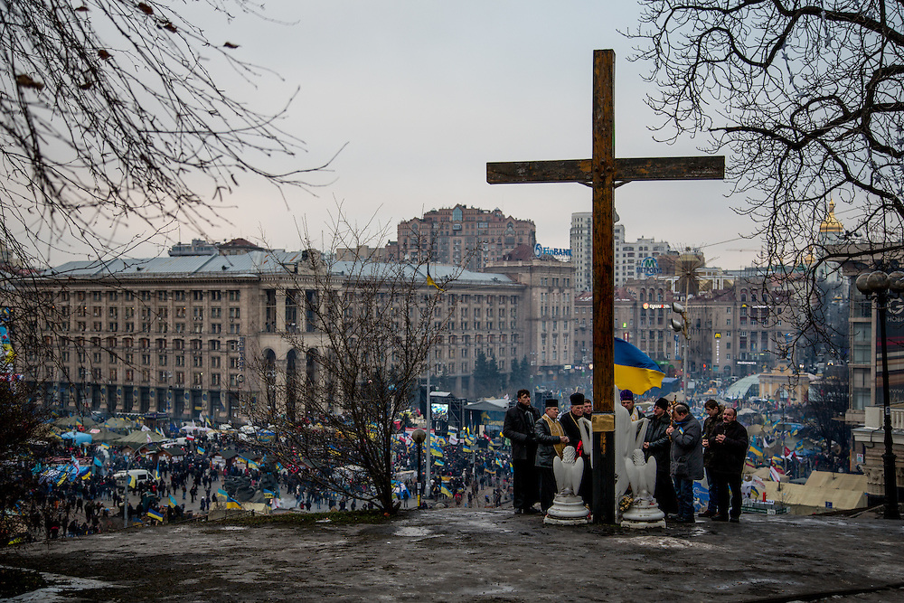 A group prays behind a giant cross, above the Independance Square.