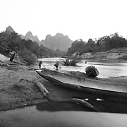 """A """"bomb boat"""" on the Senphen tributary of the Bangphai River, outside the """"bomb village"""" of Ban Senphen. The village is located in the Ban Phanhop valley, one of the """"chokes"""", or narrow corridors along the Ho Chi Minh Trail in Laos that were heavily bombed by American forces during the Vietnam War. Much of the village infrastructure, from housing supports to boats, are constructed from the metal from downed airplanes and unexploded bombs."""
