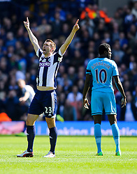 Gareth McAuley (NIR) of West Brom celebrates his sides second goal in the opening 5 minutes of the match as Emmanuel Adebayor (TOG) of Tottenham shows a look of dejection - Photo mandatory by-line: Rogan Thomson/JMP - 07966 386802 - 12/04/2014 - SPORT - FOOTBALL - The Hawthorns Stadium - West Bromwich Albion v Tottenham Hotspur - Barclays Premier League.