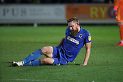 AFC Wimbledon midfielder Scott Wagstaff (7) holding his back during the EFL Sky Bet League 1 match between AFC Wimbledon and Rochdale at the Cherry Red Records Stadium, Kingston, England on 8 December 2018.