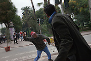 A protester throws a stone to the police during a  demonstration in the center of Tunis. People still protest against the partecipation of the Constitutional Democratic Rally, RCD, party of Ben Ali, to the national unity government . ..On 17 december Mohamed Bouazizi a fruit seller form the city of Sidibouzid in Tunisia set fire to himself starting a wave of protest that will change several arab countries under the name of Arab Spring..Despite the dictator Zine El-Abidine Ben Ali left the country on 14 January after weeks of protest the demonstrations continue asking for the political party of the regime (RCD) and all the political men involved on the past government where banned from the political life ..