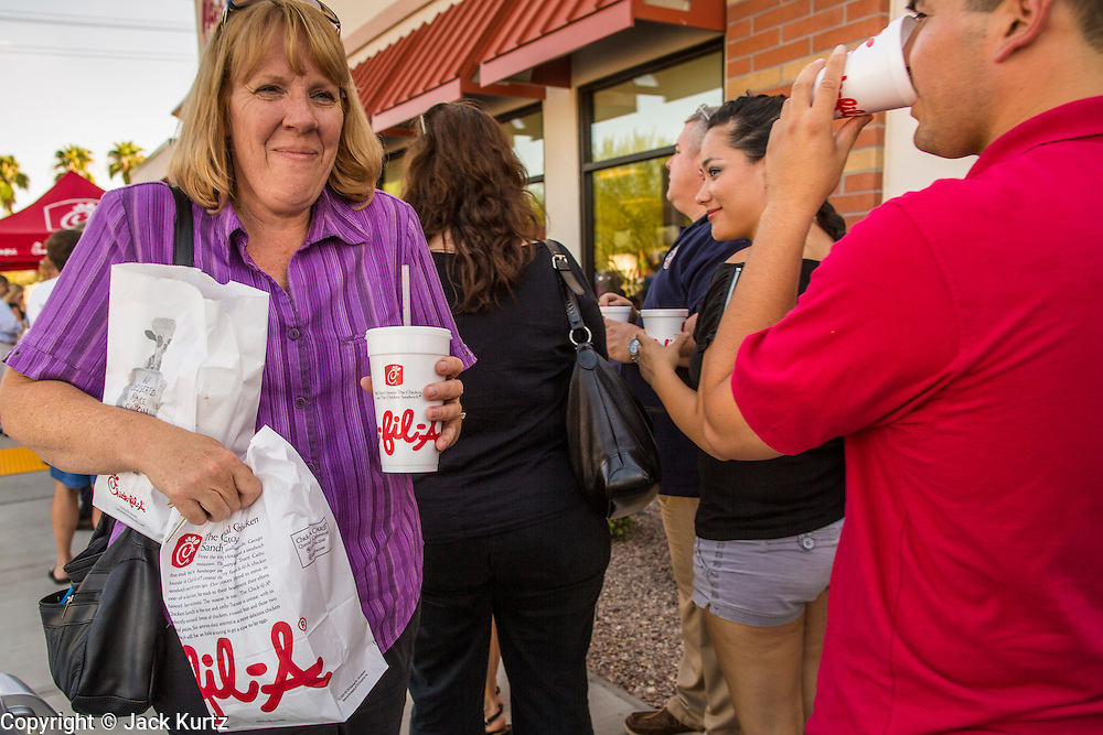 01 AUGUST 2012 - CHANDLER, AZ: A woman squeezes through the crowd after buying take out chicken at a Chick-fil-A Wednesday. Thousands of people stood in line for up to an hour at the Chick-fil-A in Chandler, AZ, a suburb of Phoenix Wednesday after MIKE HUCKABEE, the former governor of Arkansas and Fox News host, called for a national ''Chick-fil-A Appreciation Day,'' a day on which he encouraged people to patronize the fast food chain, this after DAN CATHY, President and CEO of Chick-fil-A, who is a fundamentalist Christian, made public his views against same sex marriage, causing an outcry from political leaders and Gay rights advocates.    PHOTO BY JACK KURTZ