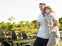 Couple embracing holding wineglasses smiling jeep in background