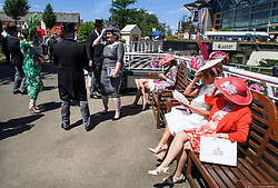 © Licensed to London News Pictures. 21/06/2018. London, UK. Racegoers rest at Ladies Day at Royal Ascot at Ascot racecourse in Berkshire, on June 21, 2018. The 5 day showcase event, which is one of the highlights of the racing calendar, has been held at the famous Berkshire course since 1711 and tradition is a hallmark of the meeting. Top hats and tails remain compulsory in parts of the course. Photo credit: Ben Cawthra/LNP