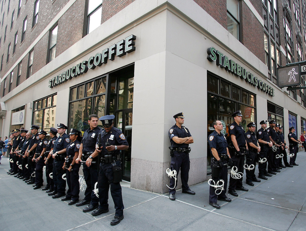 epa000264452 New York City Police officers form protective lines in front of Starbucks Coffee at 36th St. and Madison Avenue during a protest against Starbucks in New York City Saturday 28 August 2004.  Both security and protesting has increased steadily in the days leading up to the 30 August start of the Republican National Convention at New York City's Madison Square Garden.  EPA/ANDREW GOMBERT