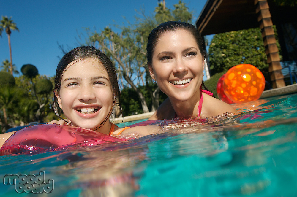 Mother and daughter smiling in swimming pool, portrait
