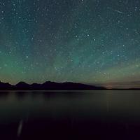 Green airglow, bright stars and mountains reflect on Jackson Lake, Grand Tetons NP
