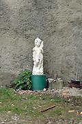 a plastic cubid garden ornament abandoned