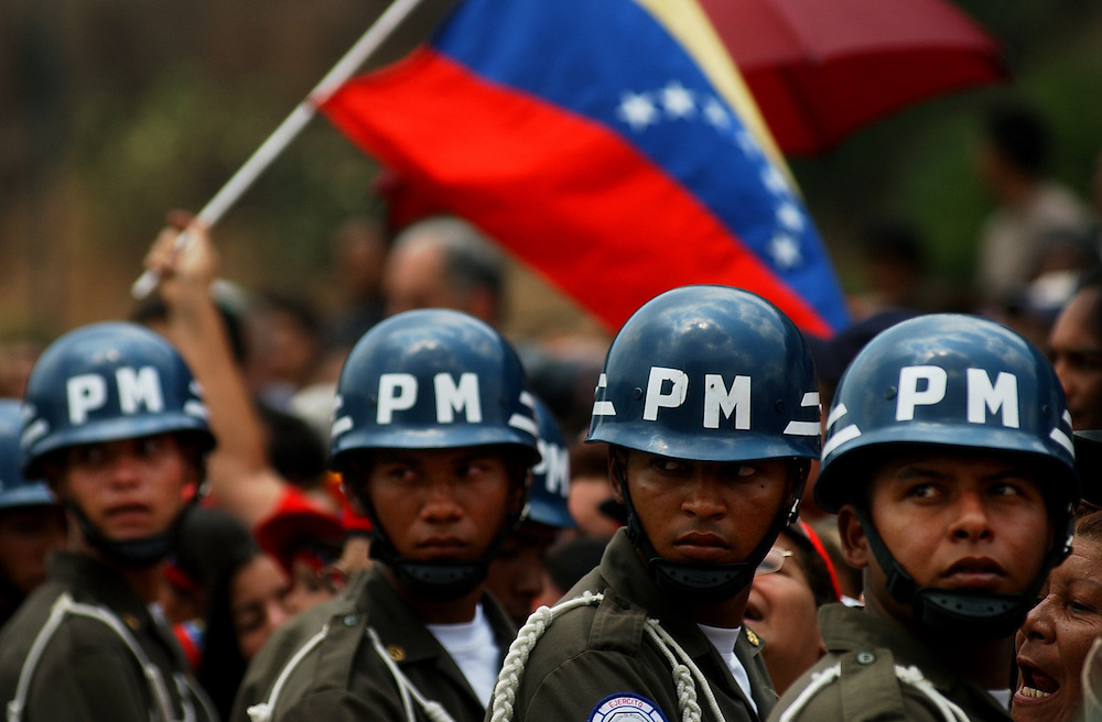Military Police hold back a crowd as President Hugo Chavez as speaks at the inaguration of a government subsidized market called Mercal.