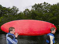 Two men carrying kayak outdoors