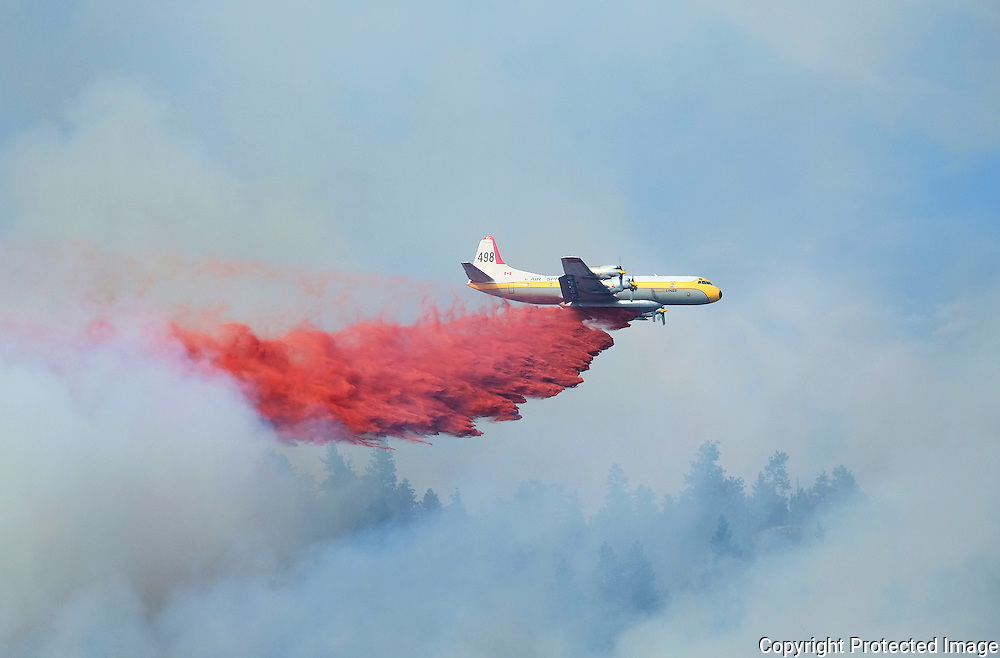 An air tanker releases fire retardant on a forest fire in Peachland, British Columbia.