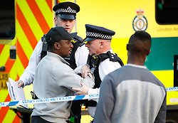 © Licensed to London News Pictures. 29/03/2019. London, UK. Police restrain a man who went through the cordon outside the Belle Vue pub next to Clapham Common tube station after a 40 year man was stabbed to death earlier this afternoon. Photo credit: Peter Macdiarmid/LNP