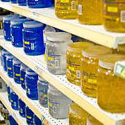 Rows of large jars of hair gel on supermarket shelves.