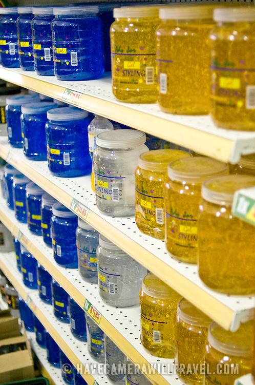 Rows of large jars of hair gel on supermarket shelves.