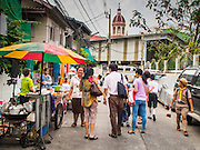 18 FEBRUARY 2015 - BANGKOK, THAILAND: The spire of Santa Cruz Catholic church is visible in the background as people buy food from street vendors on Soi Thetsaban Sai 1 in the Kudeejeen neighborhood in Bangkok. Santa Cruz church was established in 1770 and is the heart of the community. It is one of the oldest and most historic Catholic churches in Thailand. The church was originally built by Portuguese soldiers allied with King Taksin the Great. Taksin authorized the church as a thanks to the Portuguese who assisted the Siamese during the war with Burma. Most of the Catholics in the neighborhood trace their family roots to the original Portuguese soldiers who married Siamese (Thai) women. There are about 300,000 Catholics in Thailand in about 430 Catholic parishes and about 660 Catholic priests in Thailand. Thais are tolerant of other religions and although Thailand is officially Buddhist, Catholics are allowed to freely practice and people who convert to Catholicism are not discriminated against.   PHOTO BY JACK KURTZ