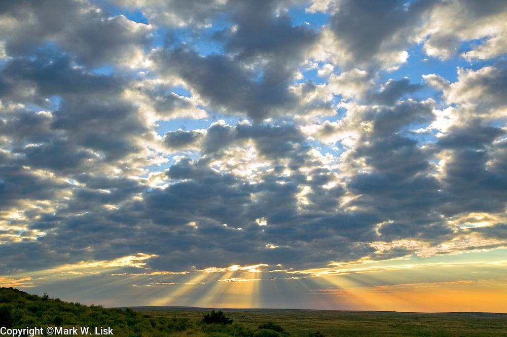 Sun rays burst from the morning sky onto the dry desert floor of southern Idaho's Owyhee Desert.