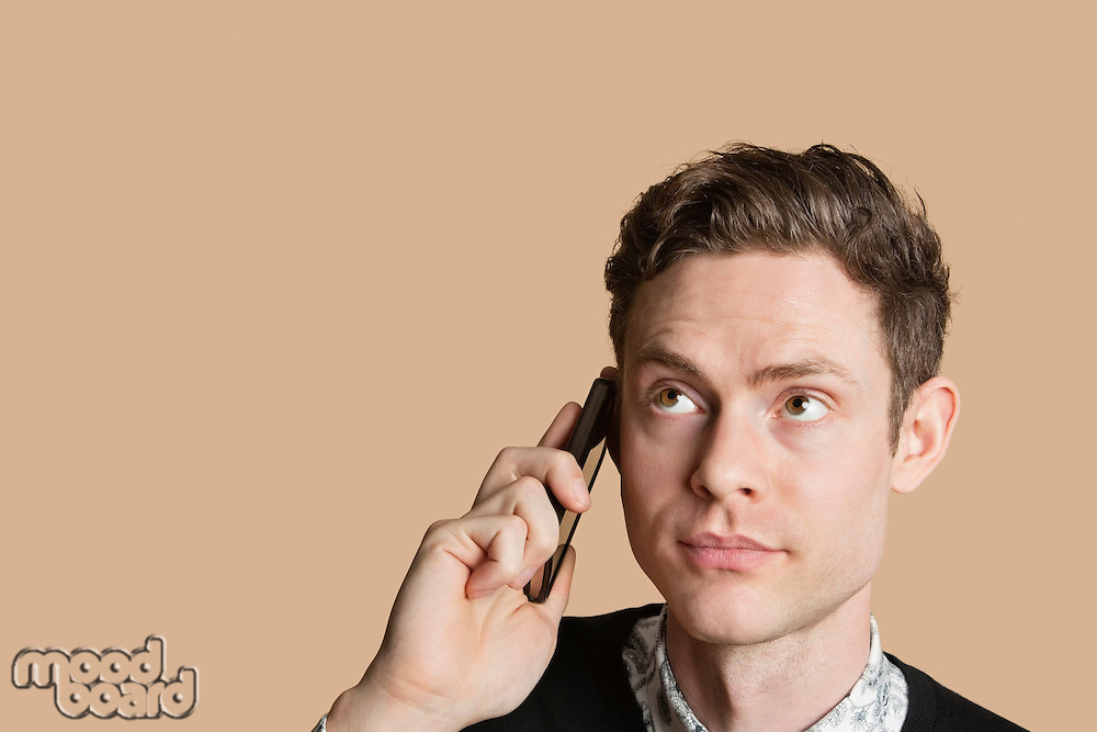 Mid adult man listening to mobile phone over colored background