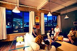 Stock photo of a group of friends enjoying the evening with drinks at a loft in downtown Houston Texas