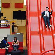 Google and YouTube Manager Global Communications Chris Dale slides down red slide at one of the hippest, most coveted - but also controversial - corporate environments on the planet in San Bruno, Californai.