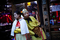 A picture made available on 05 April 2012 of a performer in a Monkey God costume and a bar staff stands wait for customers outside a bar in the Old Town of Lijiang in Yunnan Province, China, 05 April 2012. Designated a World Heritage site by UNESCO in 1997, the Old Town of Lijiang is famous for its unique architecture of the Naxi ethnic minority group and ancient waterways network. Rebuilt after being badly damaged in an earthquake in 1996, the picturesque old town is now a major tourist attraction housing a myriad of shops and bars catering to the hordes of tourists that descend on the town every year.