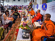 """14 FEBRUARY 2017 - BANGKOK, THAILAND: Buddhist monks bless marriages during a mass wedding in the Bang Rak district in Bangkok. Bang Rak is a popular neighborhood for weddings in Bangkok because it translates as """"Village of Love."""" (Bang translates as village, Rak translates as love.) Hundreds of couples get married in the district on Valentine's Day, which, despite its Catholic origins, is widely celebrated in Thailand.     PHOTO BY JACK KURTZ"""