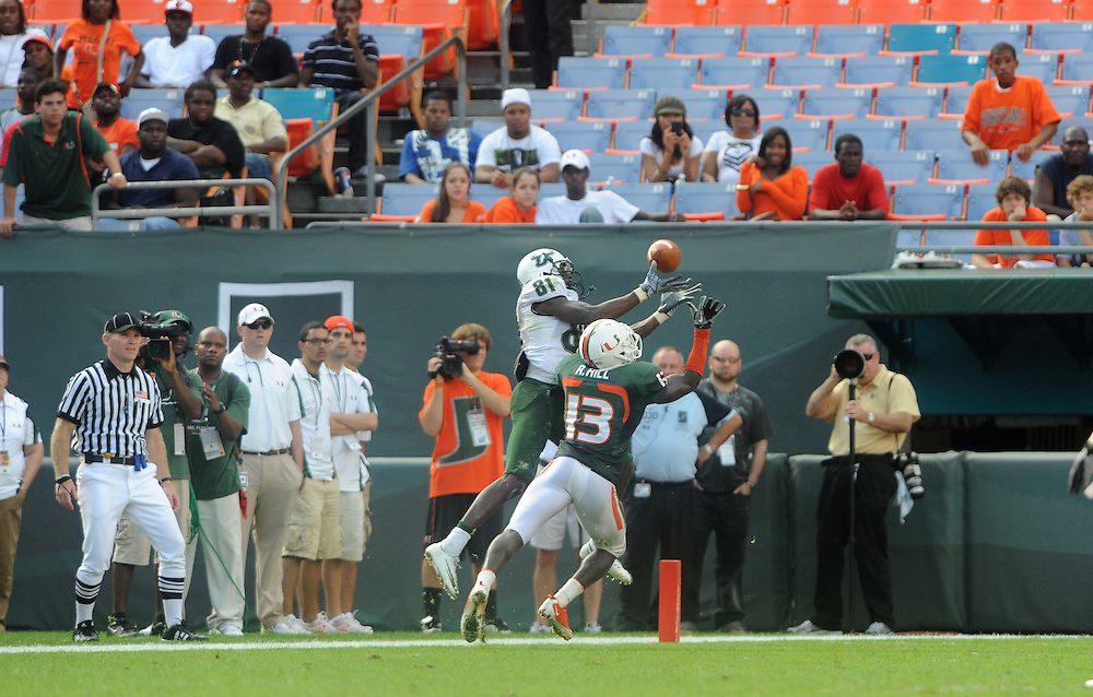 MIAMI GARDENS, FL - NOVEMBER 27: Dontavia Bogan #81 of the South Florida Bulls catches a pass as Ryan Hill #13 of the Miami Hurricanes defends during the game against the Miami Hurricanes at Sun Life Stadium in Miami Gardens, Florida on November 27, 2010. South Florida defeated the Hurricanes 23-20.