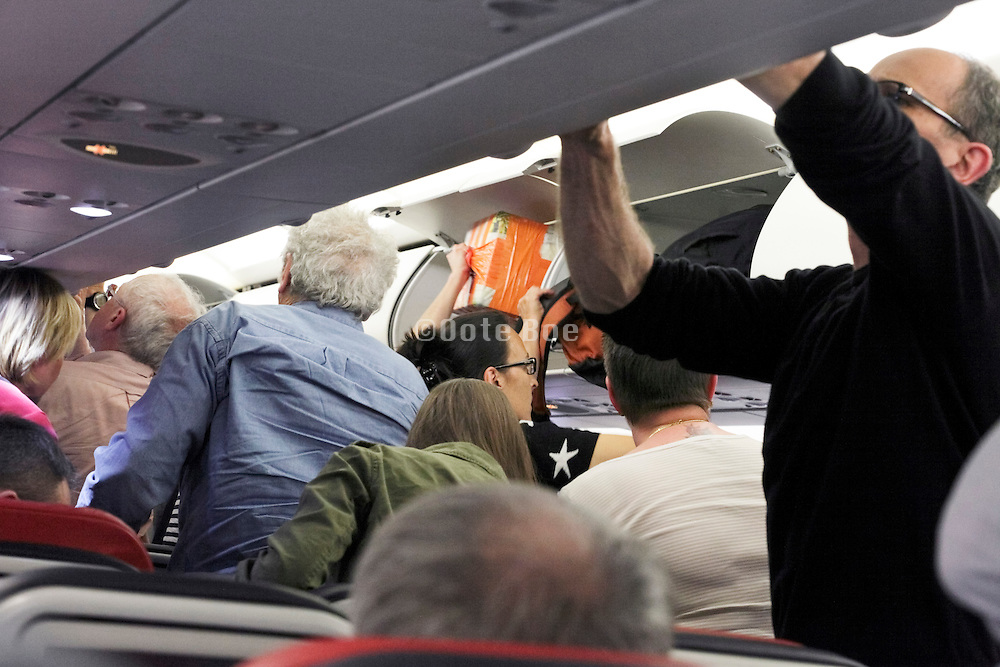 airplane passenger getting their overhead luggage