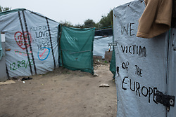 October 24, 2016 - Calais, France - ''We are victim of Europe'' ist written on a door in Calais Jungle, on October 24, 2016. After registration, the migrants are distributed on buses. The refugee camp on the coast to the English Channel is to be cleared today. The approximately 8,000 refugees are distributed after the registration by busses to various reception centers in France, on October 24, 2016. (Credit Image: © Markus Heine/NurPhoto via ZUMA Press)