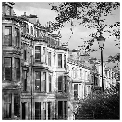 Black and white photograph of tenements in the West End of Glasgow, available to purchase as a mounted print.