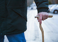Closeup of mans hand on a walking cane.