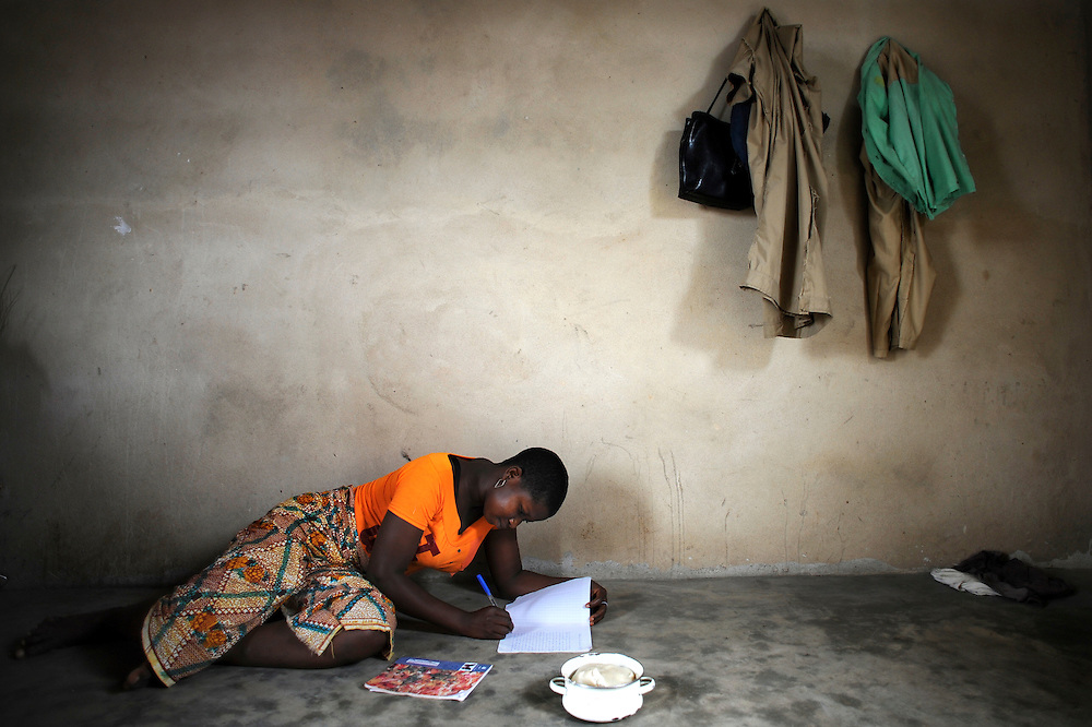 A teenager does her homework on the floor of the room in Cotonou, Benin February 29, 2008.