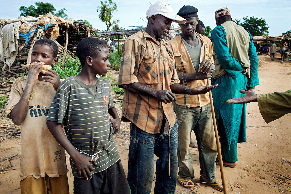 A guard, a middlemen and two young workers are inspecting the gold retrieved on behalf of a gold trader, (in green) in an artisanal gold processing site near Bagega, pop. 9000, a large village affected by lead poisoning due to the unsafe techniques employed for extracting gold, in Zamfara State, Nigeria. The contamination is caused by ingestion and breathing of lead particles released in the steps to isolate the gold from other metals. This type of lead is soluble in stomach acid and children under-5 are most affected, as they tend to ingest more through their hands by touching the ground, and are developing symptoms often leading to death or serious disabilities.
