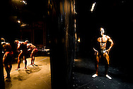 For two years in a row, in a rundown theater in Porto, the Portuguese National Championship of Bodybuilding WABBA happened. Several athletes, from allover the country came to this one day competition. <br /> These are photos from the backstage, where the athletes exercise and get body paint for the stage presentation. The muscles and the gold and brown colors get ready in the confusion of tubes, abandoned wood from different theater plays, photos from the past and dressing rooms with 100 years old. M&aacute;rio posing behind the stage.