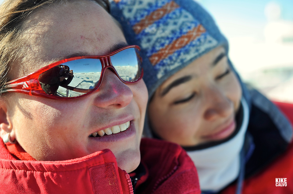 Couple of friends enjoy the sun rays in Antarctica. Sunglass reflects the photographer taking the photo. Model Released photo.