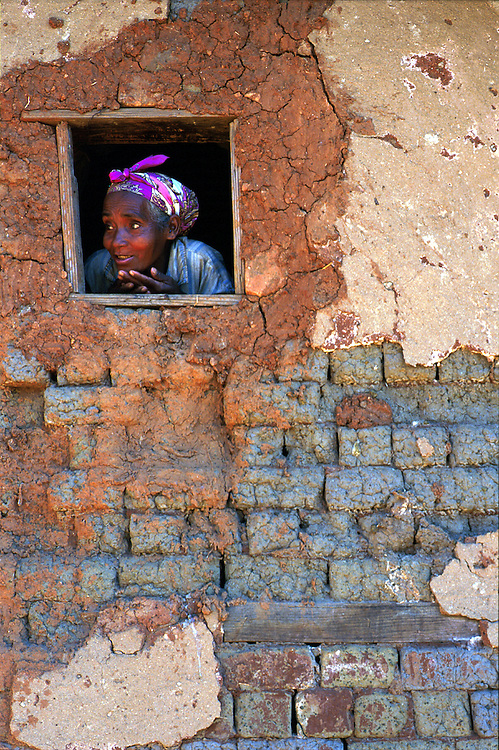 A local woman peers from her mud hut in the Fianarantsua highlands.
