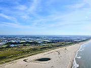Nederland, Zuid-Holland, Gemeente Westland, 14-09-2019; Delflandse Kust ter hoogte van Ter Heijde en Monster, Maasvlakte en Tweede Maasvlakte (MV2) aan de horizon. De Zandmotor is een kunstmatig schiereiland (landtong), ontstaan door het opspuiten van zand voor de kust. Wind, golven en stroming zullen het zand langs de kust in noordelijke richting verspreiden waardoor verderop langs de kust bredere stranden en duinen ontstaan. De zandmotor is een experiment in het kader van kustonderhoud en kustverdediging.<br /> Sand Engine, artificial peninsula build by the raising of sand for the coast (near the Hague). Wind, waves and currents will distribute the sand along the coast yielding wider beaches and dunes along the coastline. The Sand Engine is a experiment for coastal maintenance of coastal defense.<br /> luchtfoto (toeslag op standard tarieven);<br /> aerial photo (additional fee required);<br /> copyright foto/photo Siebe Swart