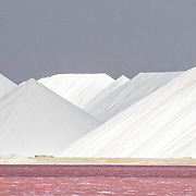 Giant mountains of slat on the southern coast of the island of Boniare. The vivid pink color comes from the salt-loving bacteria, or halobacteria, found in the salt ponds. Salt production is a major industry in Bonaire and the salt ponds are home to one of the largest breeding colonies of Caribbean flamingos.