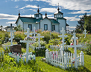 "The Russian Orthodox Church in the town of Ninilchik was redesigned and constructed in 1901 in Alaska, USA. In the graveyard, notice that the Russian Orthodox Cross has two extra arms: the top arm represents the inscribed acronyms [ INRI in Latin,  in Greek, and a Hebrew version, meaning ""Jesus the Nazarene, King of the Jews"" ], and the angled bottom arm is his footrest. Russian Orthodox religion was born in Kiev in the ""land of the Rus"" in 988 AD as a branch of Eastern Orthodox Christianity. After Russian discovery of Alaska and the Aleutian Islands in 1741, Russian fur traders taught Christianity to Alaskan Natives. The first eight Russian Orthodox missionaries came to Kodiak Island, Alaska (Russian America) in 1794. The religion spread amongst Alaskans, and the monks mission was made a diocese of the Russian Orthodox Church a few years after the United States purchased Alaska from Russia in 1867. Ninilchik is on the Sterling Highway on the west side of the Kenai Peninsula on the coast of Cook Inlet, 186 miles by road from Anchorage and 38 miles from Homer. The Alaska Native Claims Settlement Act recognized Ninilchik as an Alaska Native village. Ninilchik hosts the annual Kenai Peninsula State Fair."
