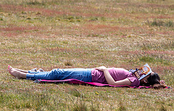 © Licensed to London News Pictures. 17/05/2020. London, UK. A women has a snooze while out in the warm air as members of the public relax in the sunshine on Wimbledon Common in South West London on the first weekend after the Government relaxed the law on lockdown to let people spend more time outside as weather experts predict 25c for the week ahead. Photo credit: Alex Lentati/LNP