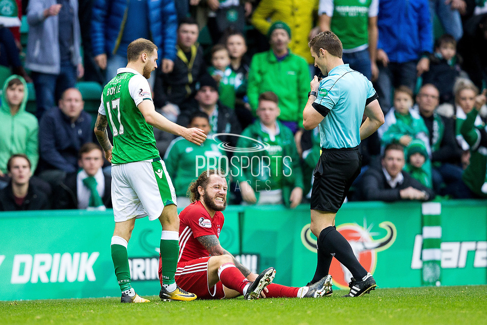 Aberdeen forward Stevie May (#83) sits down injured after fouling Hibernian forward Martin Boyle (#17) during the Ladbrokes Scottish Premiership match between Hibernian and Aberdeen at Easter Road, Edinburgh, Scotland on 14 October 2017. Photo by Craig Doyle.