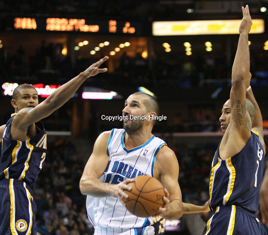 Feb 19, 2010; New Orleans, LA, USA; New Orleans Hornets forward Peja Stojakovic (16) drives between Indiana Pacers guard Earl Watson (2) and guard Dahntay Jones (1) during the second half at the New Orleans Arena. The Hornets defeated the Pacers 107-101.  Mandatory Credit: Derick E. Hingle-US PRESSWIRE