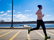 """29 MARCH 2020 - DES MOINES, IOWA:Joggers on an empty running trail around Gray's Lake, a popular park and lake near downtown Des Moines Sunday. On Sunday morning, 29 March, Iowa reported 336 confirmed cases of the Novel Coronavirus (SARS-CoV-2) and COVID-19. There have been four deaths attributed to COVID-19 in Iowa. Restaurants, bars, movie theaters, places that draw crowds are closed until 07 April. The Governor has not ordered """"shelter in place""""  but several Mayors, including the Mayor of Des Moines, have asked residents to stay in their homes for all but the essential needs. People are being encouraged to practice """"social distancing"""" and many businesses are requiring or encouraging employees to telecommute.       PHOTO BY JACK KURTZ"""