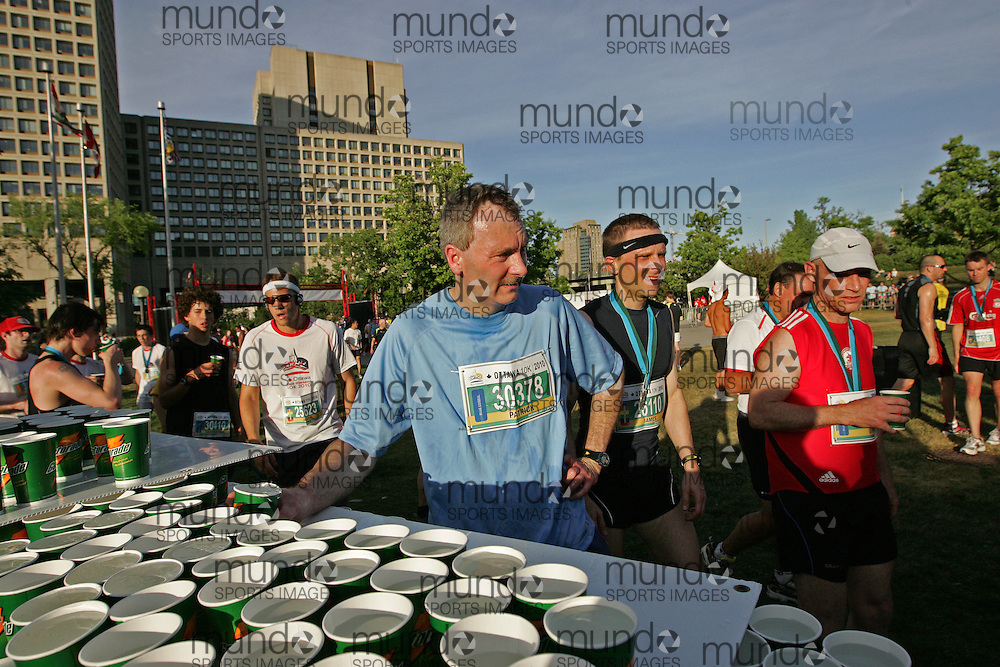 (Ottawa, ON --- May 29, 2010) PATRICK LEAHY getting water after the 10km race during the Ottawa Race Weekend. Photograph copyright Sean Burges / Mundo Sport Images