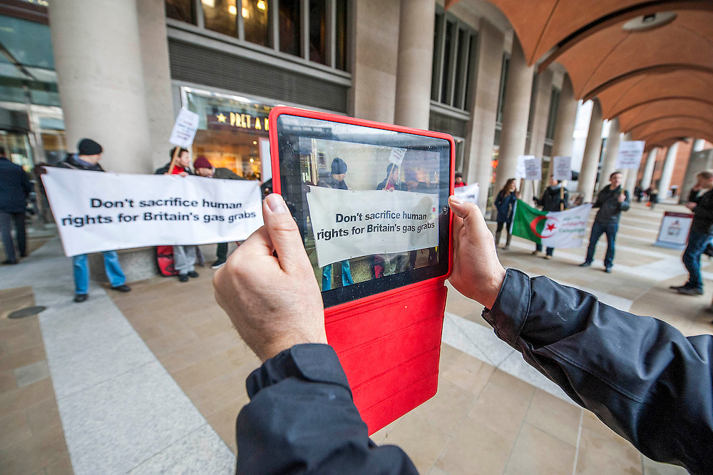 "Spreading the message using new media - i-pad to Youtube. Human rights protestors from the Algeria Solidarity Campaign (ASC) gather outside the London Stock Exchange to raise awareness about what they call 'the repressive Algerian regime' and its links with powerful multinationals such as BP who are keen on its gas reserves. Inside there is a business conference – The Algerian Investor Window – and the protestors hope to highlight issues about ""British collusion with a repressive and corrupt regime for the sake of business interests and securing fossil fuel supplies"" with the attendees. Paternoster Square, London, UK 10 Feb 2014. Guy Bell, 07771 786236, guy@gbphotos.com"