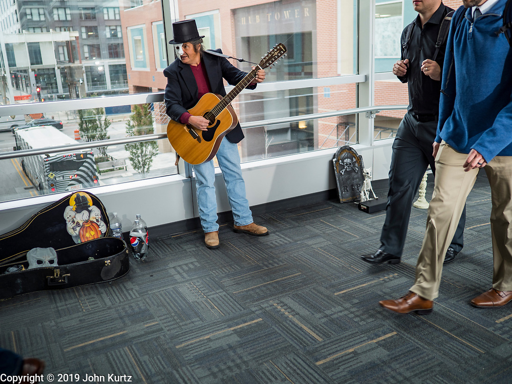 "30 OCTOBER 2019 - DES MOINES, IOWA: RANDY KONG performs in the Des Moines Skywalk system. Kong said he's been busking for about nine years. He said he started when his band broke up and busking might be way to ""get a hot dog and a coke, and now it's turned into a career."" He usually performs during the lunch hour and is a regular sight in the skywalk system. In October he hands out candy and sings Halloween themed songs while wearing a ""Phantom of the Opera"" like mask. In December he does a Christmas themed show and in February he does a Valentines themed show.        PHOTO BY JACK KURTZ"