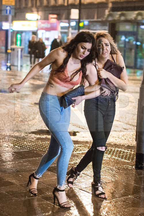 © Licensed to London News Pictures . 17/03/2017 . Cardiff , UK. A woman stumbles on the pavement as another props her up . Revellers on a windy and wet Saint Patrick's Day night out in Cardiff city Centre . Photo credit: Joel Goodman/LNP